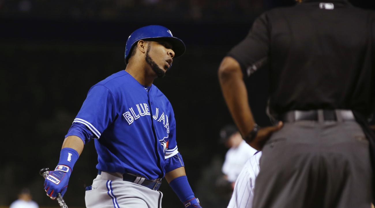 Toronto Blue Jays' Edwin Encarnacion, left, argues a called strike with home plate umpire Laz Diaz while facing Colorado Rockies starting pitcher Eddie Butler during the first inning of a baseball game Tuesday, June 28, 2016, in Denver. (AP Photo/David Za