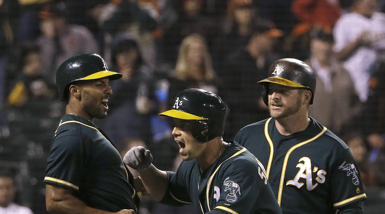 Oakland Athletics' Jake Smolinski, center, celebrates after hitting a three-run home run that scored Marcus Semien, left, and Stephen Vogt, right, against the San Francisco Giants during the eighth inning of a baseball game in San Francisco, Tuesday, June