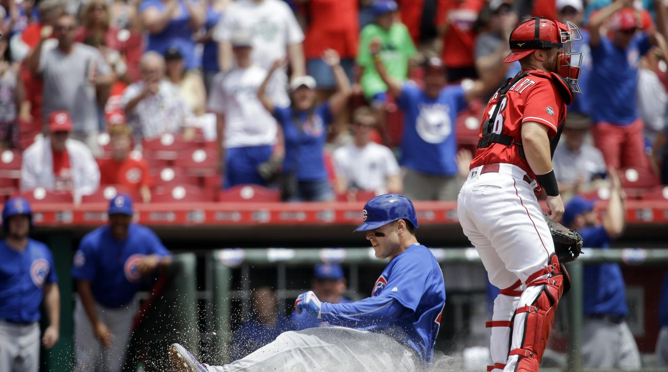 Chicago Cubs' Anthony Rizzo slides home safely with a three-run inside the park home run off Cincinnati Reds starting pitcher Cody Reed as catcher Tucker Barnhart, right, stands at home in the first inning of a baseball game, Wednesday, June 29, 2016, in