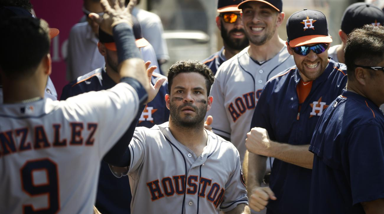 Houston Astros' Jose Altuve, center, is greeted by teammates after he scored on a single hit by Carlos Gomez during the ninth inning of a baseball game against the Los Angeles Angels, Wednesday, June 29, 2016, in Anaheim, Calif. (AP Photo/Jae C. Hong)