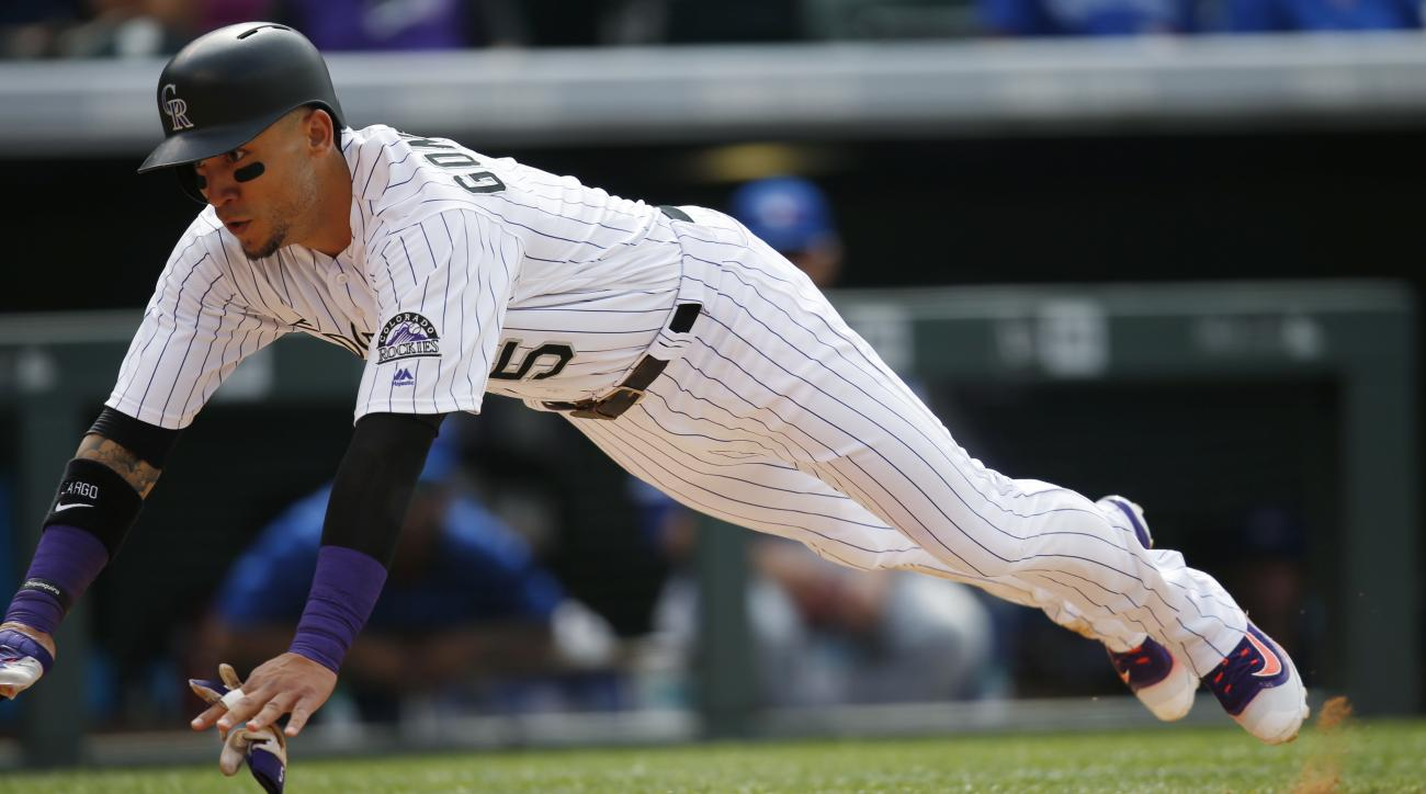 Colorado Rockies' Carlos Gonzalez dives into home plate to score on a double hit by Mark Reynolds off Toronto Blue Jays relief pitcher Roberto Osuna during the ninth inning of a baseball game Wednesday, June 29, 2016, in Denver. Toronto won 5-3. (AP Photo
