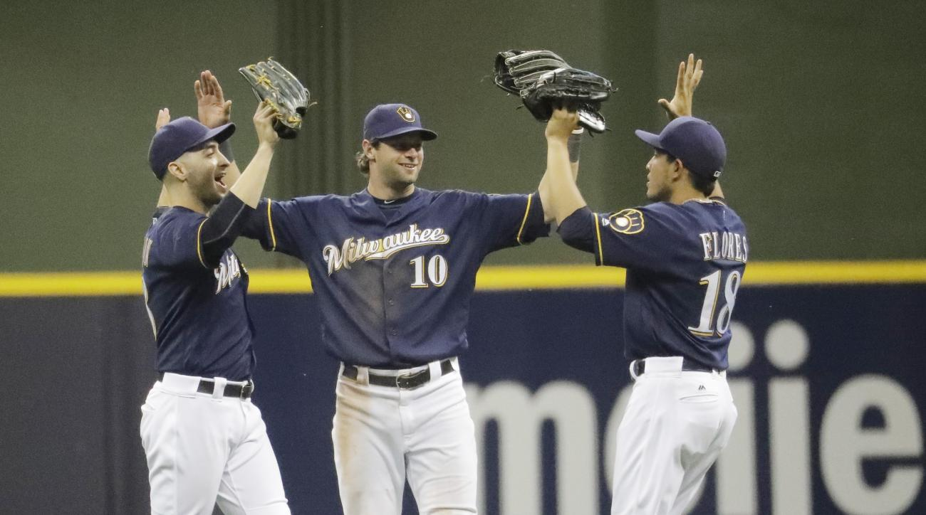 Milwaukee Brewers' Ryan Braun, Kirk Nieuwenhuis (10) and Ramon Flores (18) celebrate after a baseball game against the Los Angeles Dodgers Wednesday, June 29, 2016, in Milwaukee. The Brewers won 7-0. (AP Photo/Morry Gash)