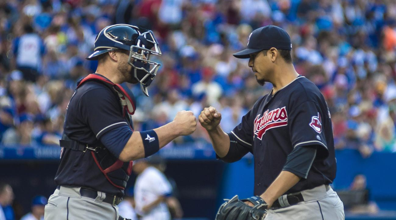 Cleveland Indians' Chris Gimenez, left, greets teammate Carlos Carrasco at the end of third inning against the Toronto Blue Jays in a baseball game Thursday, June 30, 2016, in Toronto. (Eduardo Lima/The Canadian Press via AP)