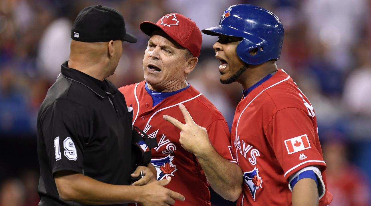 Toronto Blue Jays manager John Gibbons, center, and designated hitter Edwin Encarnacion exchange words with umpire Vic Carapazza (19) after Encarnacion was ejected from the game over a call-out on strikes during the first inning of a baseball against the
