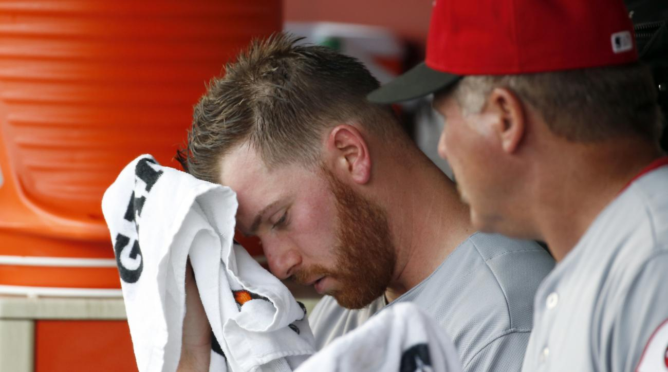 Cincinnati Reds starting pitcher Anthony DeSclafani, left, wipes his face as he listens to pitching coach Mark Riggins in the dugout during the fourth inning of a baseball game against the Washington Nationals, Friday, July 1, 2016, in Washington. (AP Pho