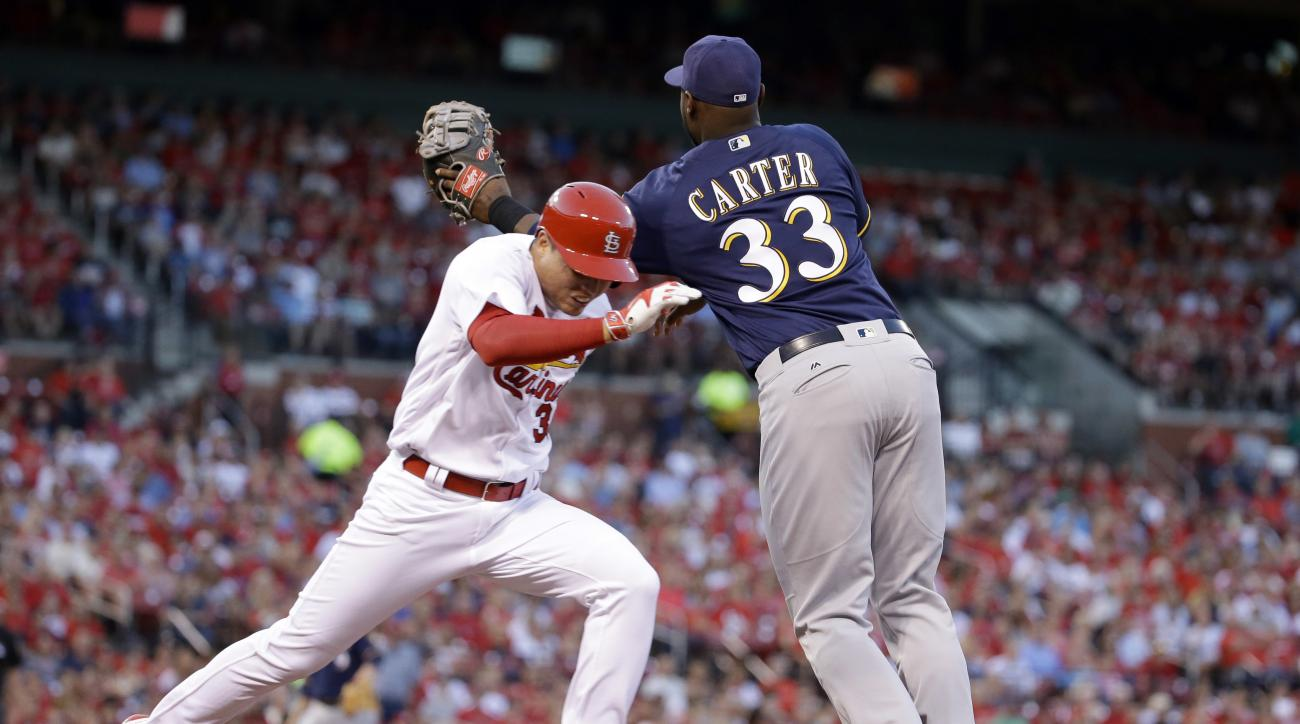 St. Louis Cardinals' Aledmys Diaz, left, is safe at first as Milwaukee Brewers first baseman Chris Carter has to come off the bag to catch a throw from shortstop Jonathan Villar during the third inning of a baseball game Friday, July 1, 2016, in St. Louis