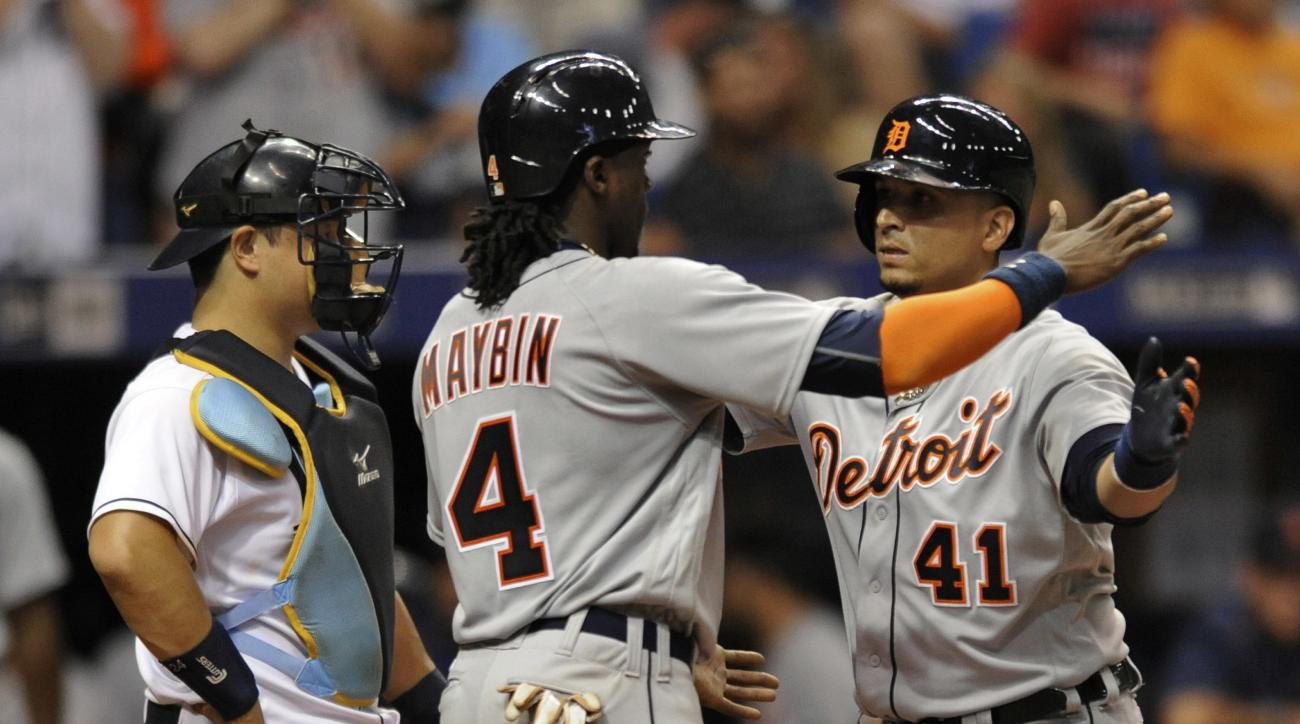 Tampa Bay Rays catcher Hank Conger looks on as Detroit Tigers' Cameron Maybin (4) celebrates with Victor Martinez (41) after Martinez' three-run homer during the seventh inning of a baseball game Friday, July 1, 2016, in St. Petersburg, Fla. (AP Photo/Ste
