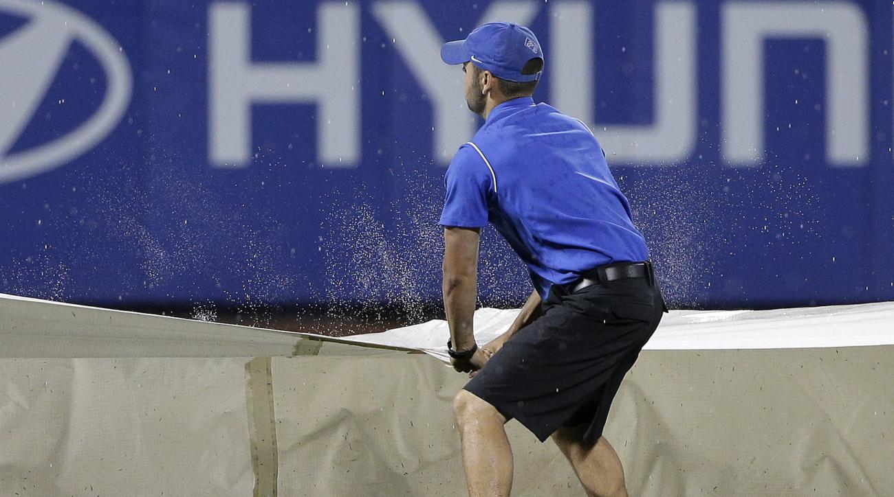 A grounds crew member shakes water off the tarp as the crew pulls the tarp out at the beginning of a rain delay during the sixth inning of a baseball game between the New York Mets and the Chicago Cubs, Friday, July 1, 2016, in New York. (AP Photo/Julie J