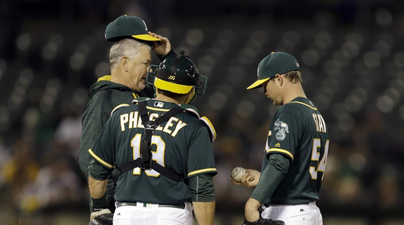 Oakland Athletics pitcher Sonny Gray, right, speaks with pitching coach Curt Young, left, and catcher Josh Phegley in the sixth inning of a baseball game against the Pittsburgh Pirates Friday, July 1, 2016, in Oakland, Calif. (AP Photo/Ben Margot)