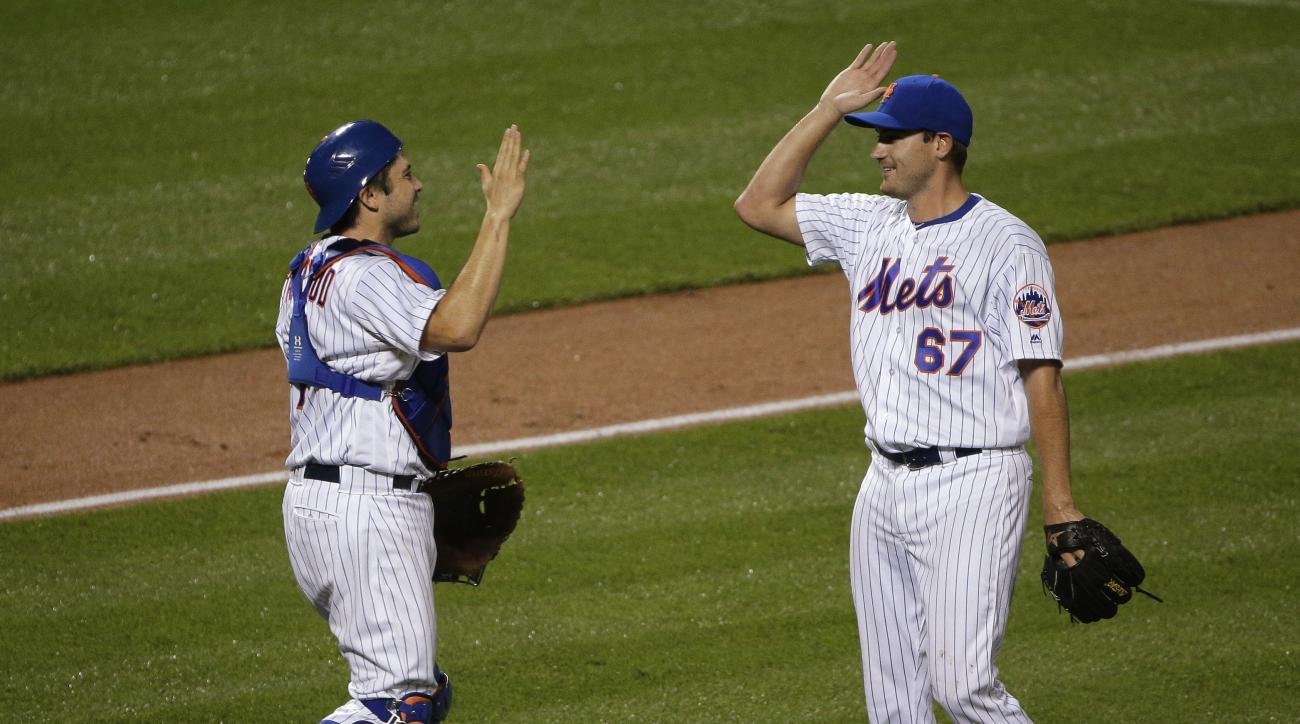 New York Mets pitcher Seth Lugo (67) celebrates with catcher Travis d'Arnaud after the Mets defeated the Chicago Cubs 10-2 in a baseball game, early Saturday, July 2, 2016, in New York. (AP Photo/Julie Jacobson)