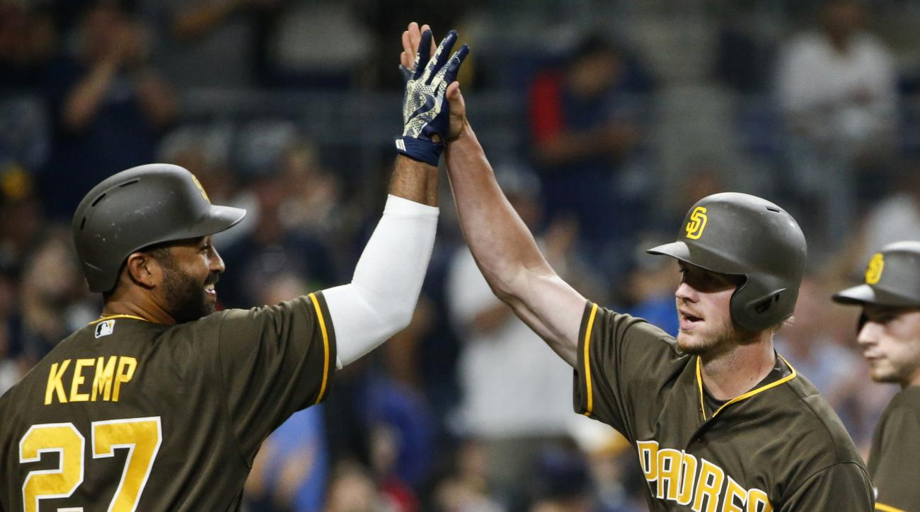 San Diego Padres' Wil Myers high-fives with Matt Kemp after Myers' two-run home run against the New York Yankees in the fifth inning of a baseball game Friday, July 1, 2016, in San Diego. (AP Photo/Lenny Ignelzi)