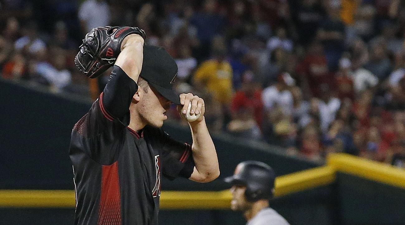 Arizona Diamondbacks' Patrick Corbin, left, adjusts his cap after giving up a home run to San Francisco Giants' Mac Williamson, right, during the fourth inning of a baseball game Saturday, July 2, 2016, in Phoenix. (AP Photo/Ross D. Franklin)