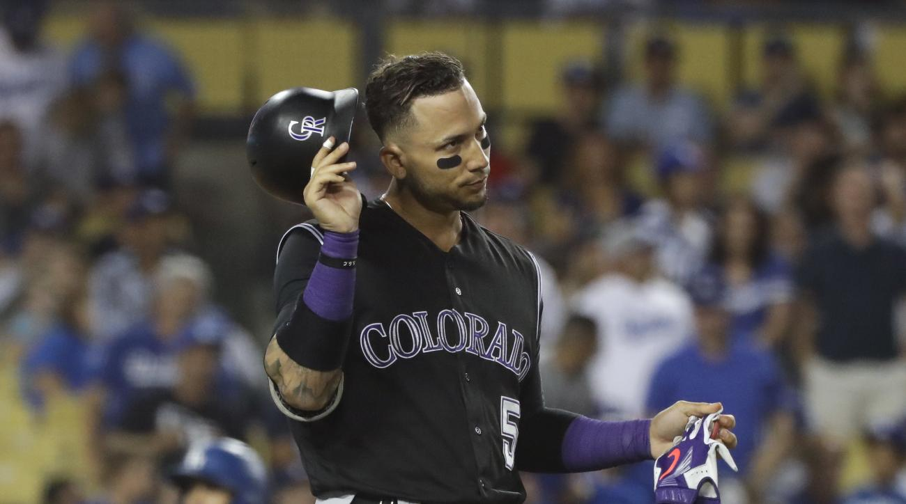 Colorado Rockies' Carlos Gonzalez takes off his helmet after striking out during the sixth inning of a baseball game against the Los Angeles Dodgers, Saturday, July 2, 2016, in Los Angeles. (AP Photo/Jae C. Hong)