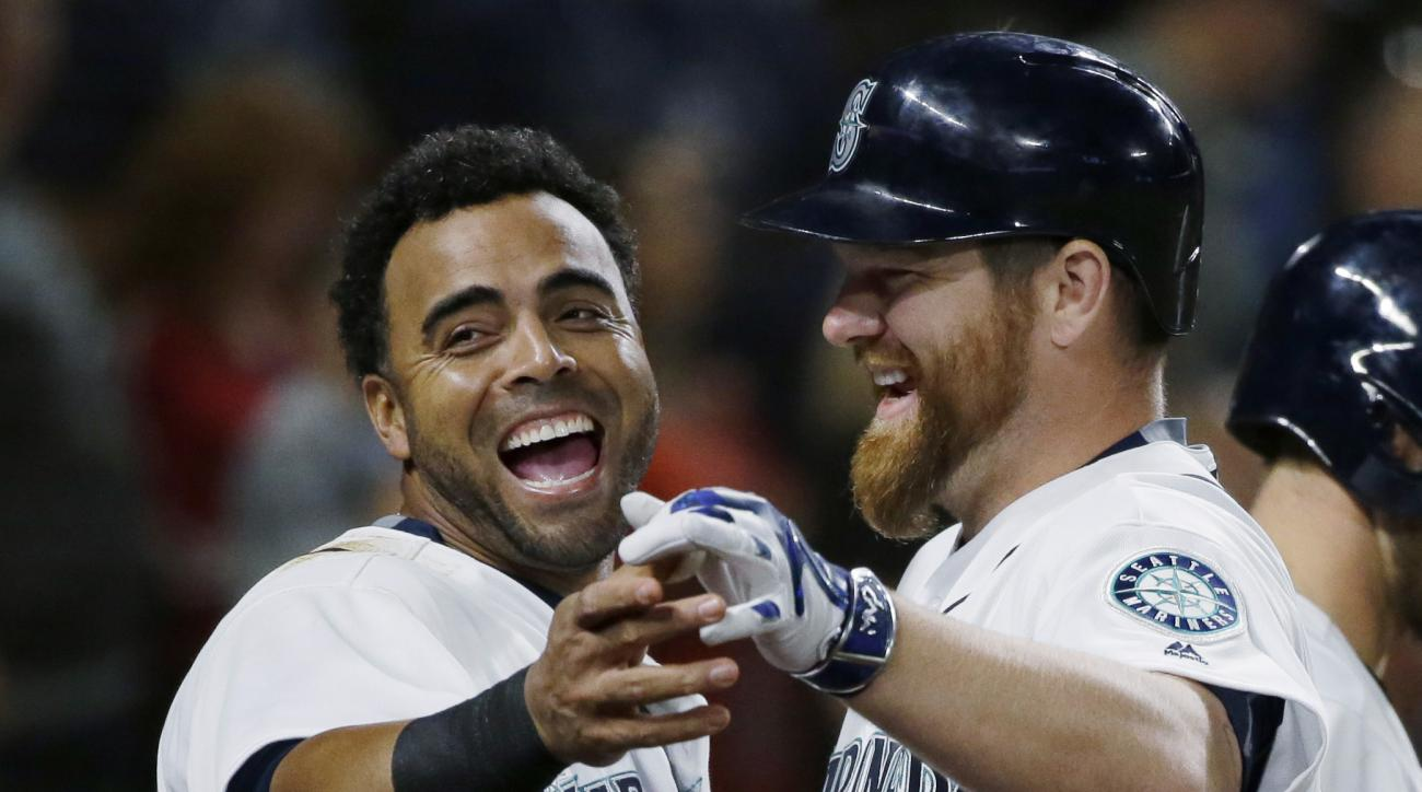 Seattle Mariners' Nelson Cruz, left, reacts as he greets Mariners' Adam Lind, right, after Lind hit a solo home run against the Baltimore Orioles during the sixth inning of a baseball game, Saturday, July 2, 2016, in Seattle. (AP Photo/Ted S. Warren)