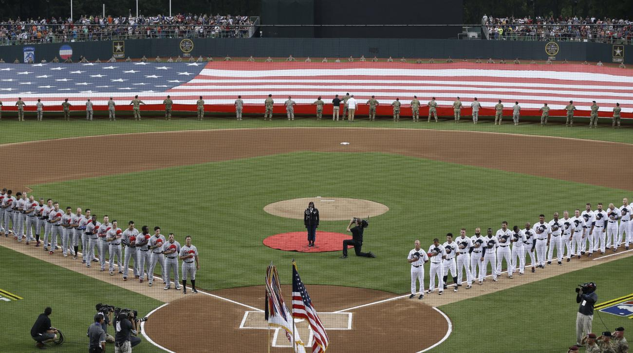 Miami Marlins and Atlanta Braves players line the base paths during the national anthem prior to a baseball game in Fort Bragg, N.C., Sunday, July 3, 2016. (AP Photo/Gerry Broome)