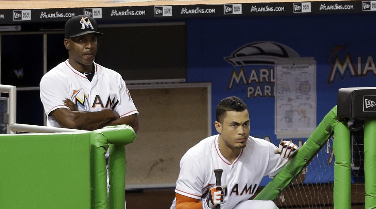 FILE - In this Friday, June 24, 2016 file photo, Miami Marlins hitting coach Barry Bonds, left, and Giancarlo Stanton watch from the dugout in the eighth inning of a baseball game against the Chicago Cubs in Miami. Bonds is enjoying his close-up view of p