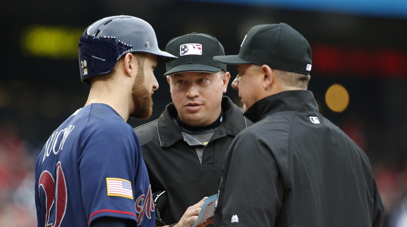 Milwaukee Brewers' Jonathan Lucroy (20) talks to home plate umpire Cory Blaser, center, and umpire Jeff Nelson after an issue was raised with the batting order during the first inning of a baseball game against the Washington Nationals at Nationals Park,