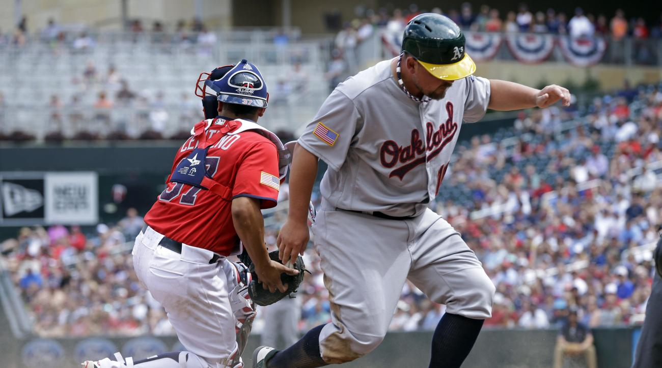 Oakland Athletics' Billy Butler, right, beats the tag by Minnesota Twins' Juan Centeno to score on a two-run single by Coco Crisp off Twins pitcher Taylor Rogers in the seventh inning of a baseball game Monday, July 4, 2016, in Minneapolis. (AP Photo/Jim