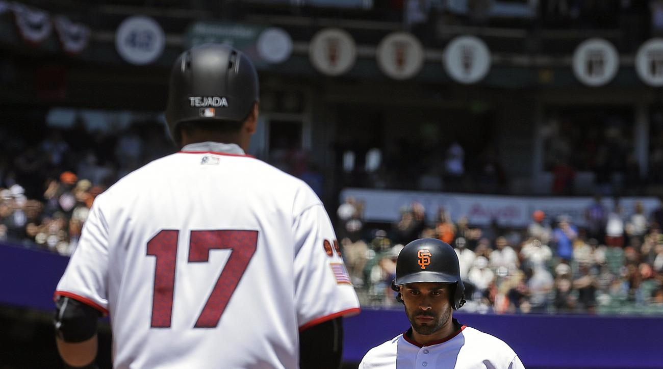 San Francisco Giants' Ruben Tejada (17) waits for Angel Pagan, right, to cross home plate after Pagan hit a two-run home run off Colorado Rockies' Tyler Anderson in the third inning of a baseball game Monday, July 4, 2016, in San Francisco. (AP Photo/Ben