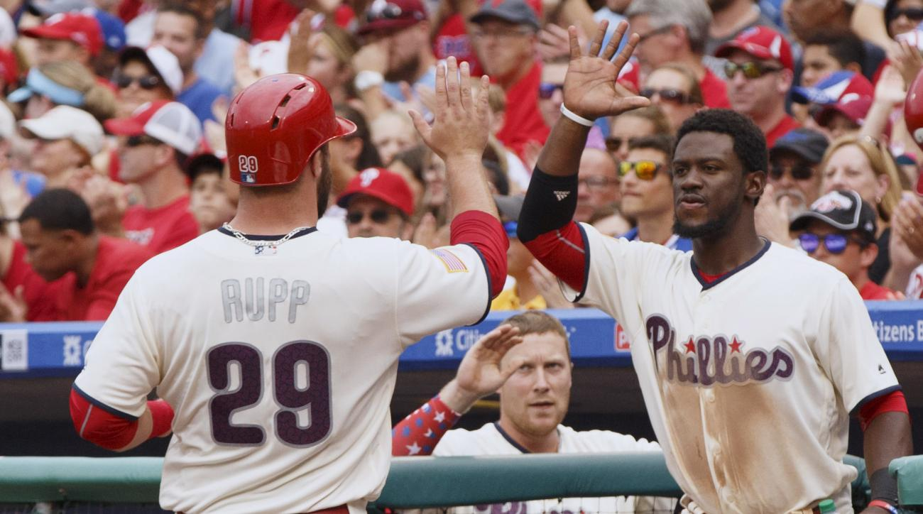 Philadelphia Phillies' Cameron Rupp, left, celebrates scoring on the hit by Tommy Joseph with Odubel Herrera, right, during the second inning of a baseball game against the Atlanta Braves, Monday, July 4, 2016, in Philadelphia. (AP Photo/Chris Szagola)