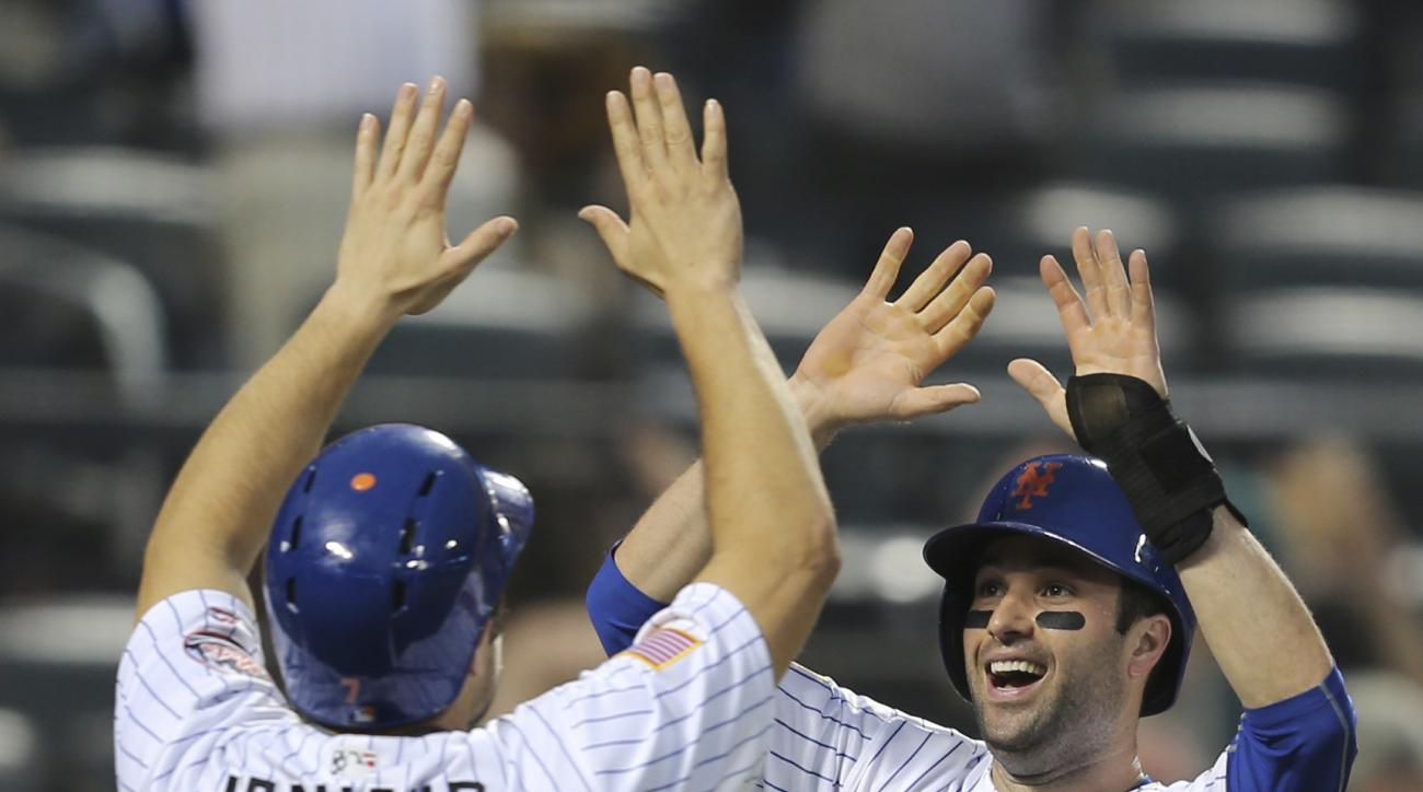 New York Mets' Neil Walker, right, and Travis d'Arnaud celebrate scoring on a double hit by Yoenis Cespedes during the eighth inning of the baseball game against the Miami Marlins, Monday, July 4, 2016 in New York. (AP Photo/Seth Wenig)