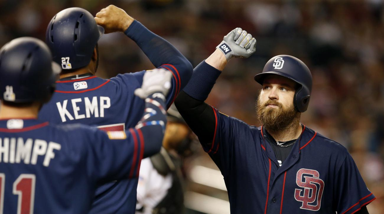 San Diego Padres' Derek Norris, right, celebrates with Matt Kemp and Ryan Schimpf, left, after hitting a three-run home run against the Arizona Diamondbacks in the sixth inning during a baseball game Monday, July 4, 2016, in Phoenix. (AP Photo/Rick Scuter