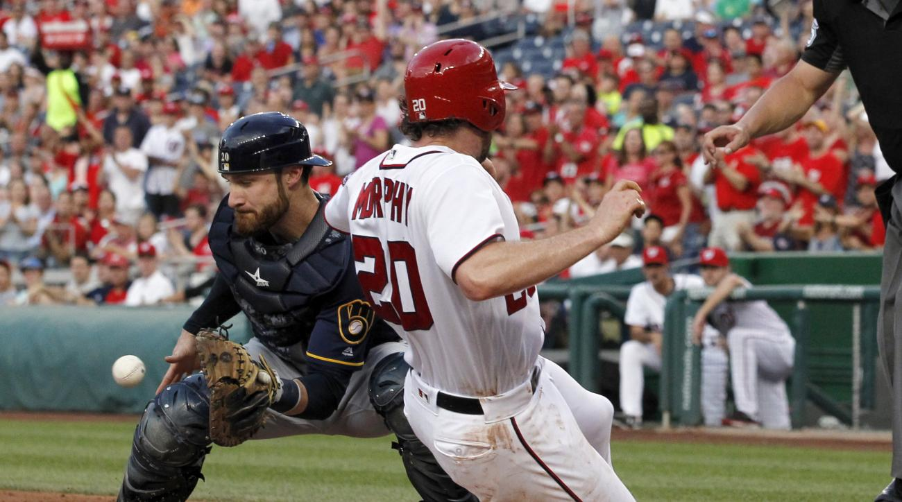 Milwaukee Brewers catcher Jonathan Lucroy waits for the throw as Washington Nationals' Daniel Murphy (20) slides safely into home on a single by Anthony Rendon during the second inning of a baseball game at Nationals Park, Tuesday, July 5, 2016, in Washin
