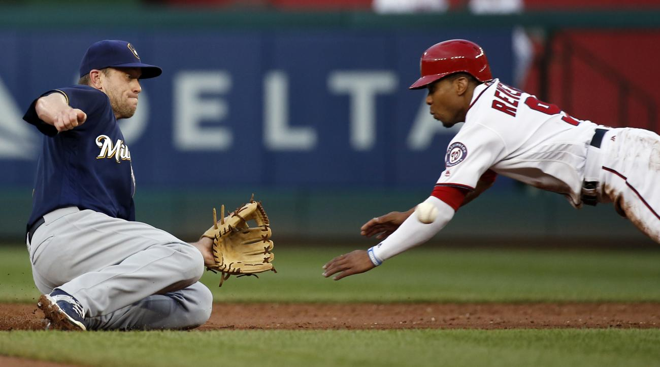 Milwaukee Brewers second baseman Aaron Hill waits for the throw from catcher Jonathan Lucroy and makes the tag for the out on Washington Nationals' Ben Revere on the steal attempt of second base during the third inning of a baseball game at Nationals Park