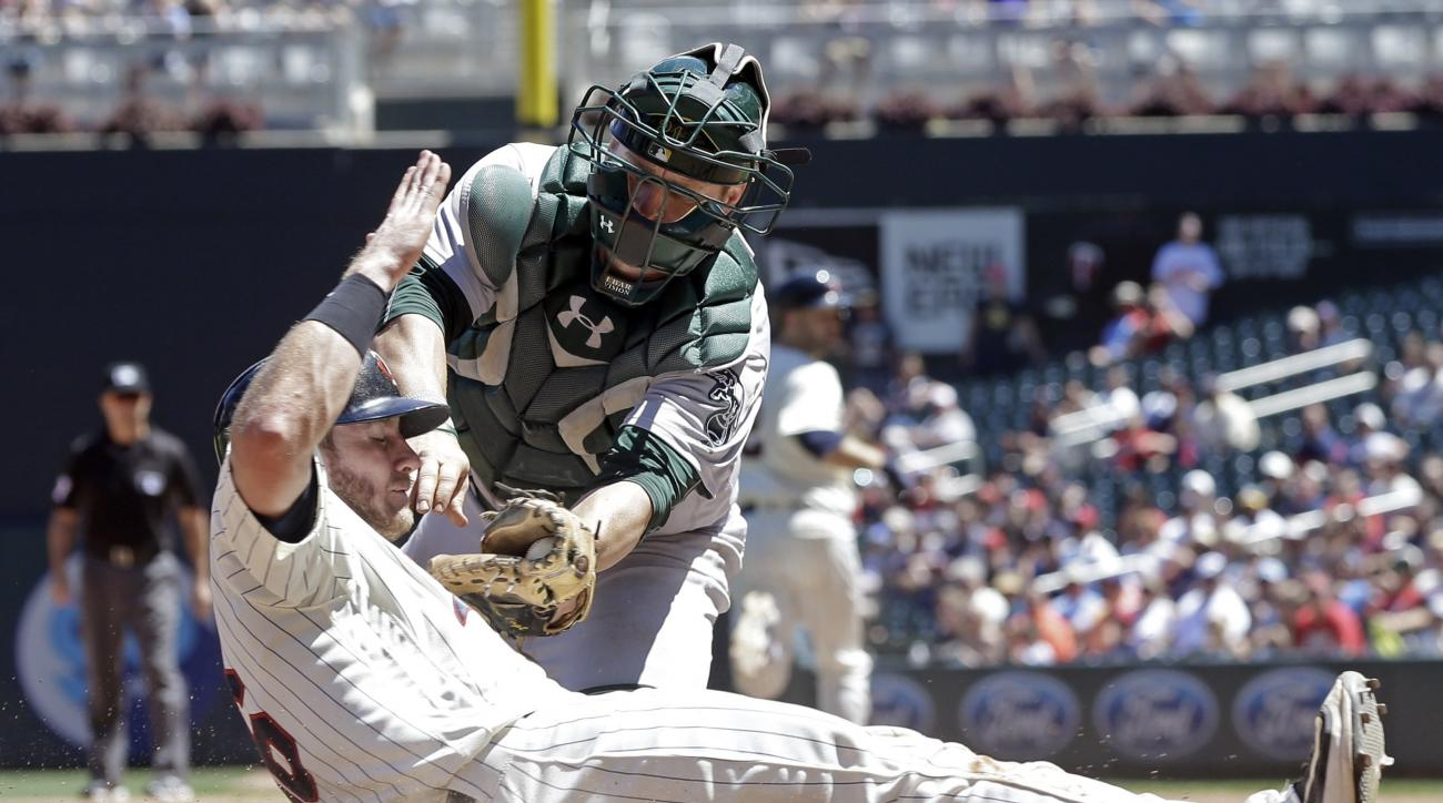 Minnesota Twins' Robbie Grossman, left, is tagged out at the plate by Oakland Athletics catcher Stephen Vogt in the seventh inning on a fielder's choice in a baseball game Wednesday, July 6, 2016, in Minneapolis. (AP Photo/Jim Mone)