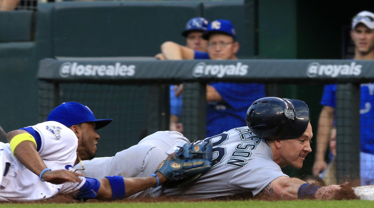 Seattle Mariners' Dan Robertson (99) is tagged out by Kansas City Royals shortstop Alcides Escobar (2) after getting caught in a rundown during the second inning of a baseball game at Kauffman Stadium in Kansas City, Mo., Thursday, July 7, 2016. (AP Photo