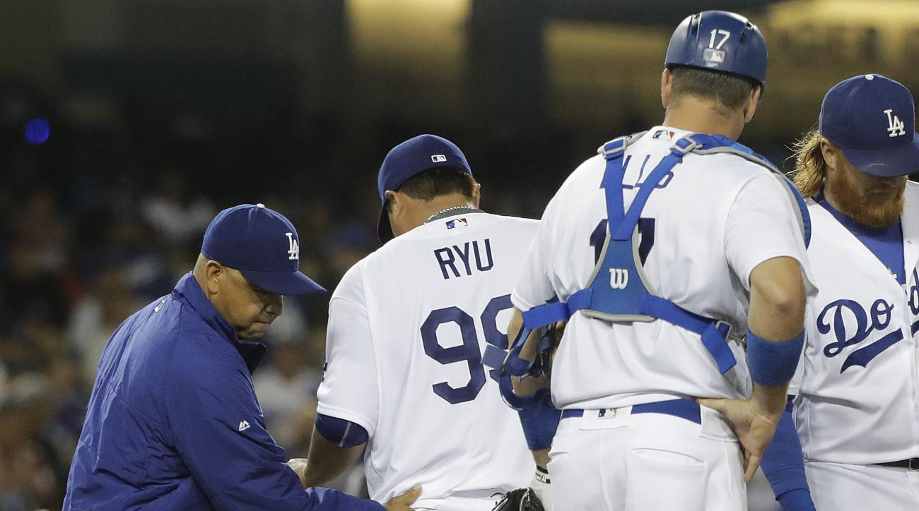 Los Angeles Dodgers manager Dave Roberts, left, relieves starting pitcher Hyun-Jin Ryu, center, of South Korea, as catcher A.J. Ellis watches during the fifth inning of a baseball game against the San Diego Padres, Thursday, July 7, 2016, in Los Angeles.