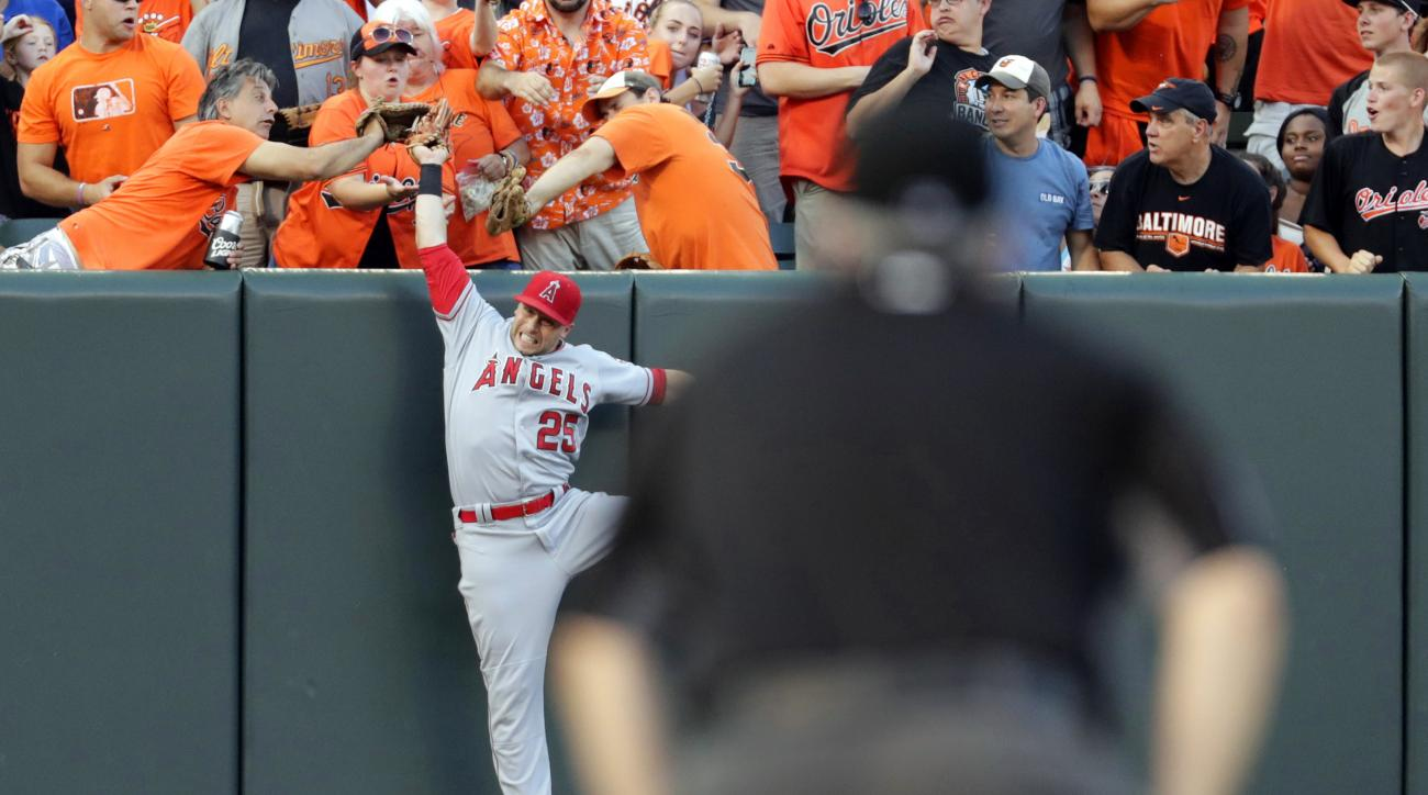 Los Angeles Angels left fielder Daniel Nava is seen past third base umpire Paul Emmel as he catches a fly ball by Baltimore Orioles' Manny Machado in the first inning of a baseball game in Baltimore, Friday, July 8, 2016. (AP Photo/Patrick Semansky)