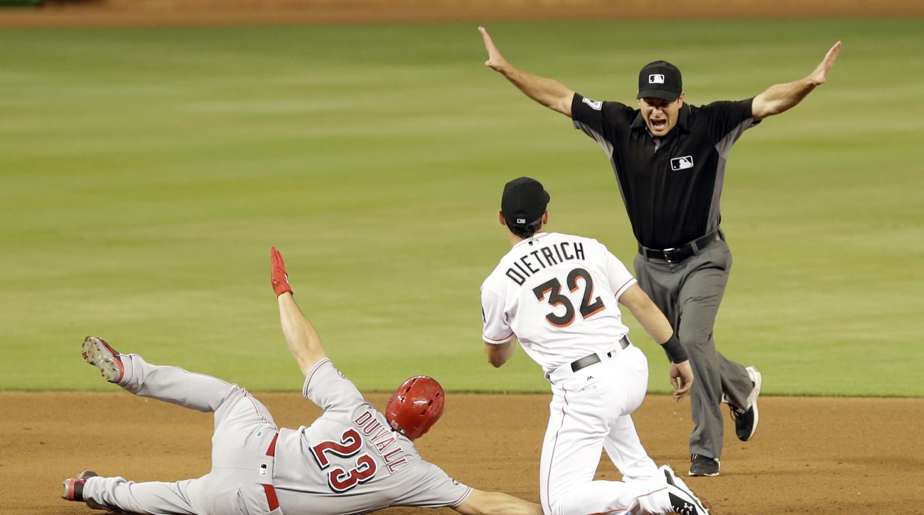 Cincinnati Reds' Adam Duvall (23) is called safe by second base umpire Ben May, right, as Miami Marlins second baseman Derek Dietrich (32) looks at May after Duvall hit a base hit in the fourth inning of a baseball game, Friday, July 8, 2016. (AP Photo/Al