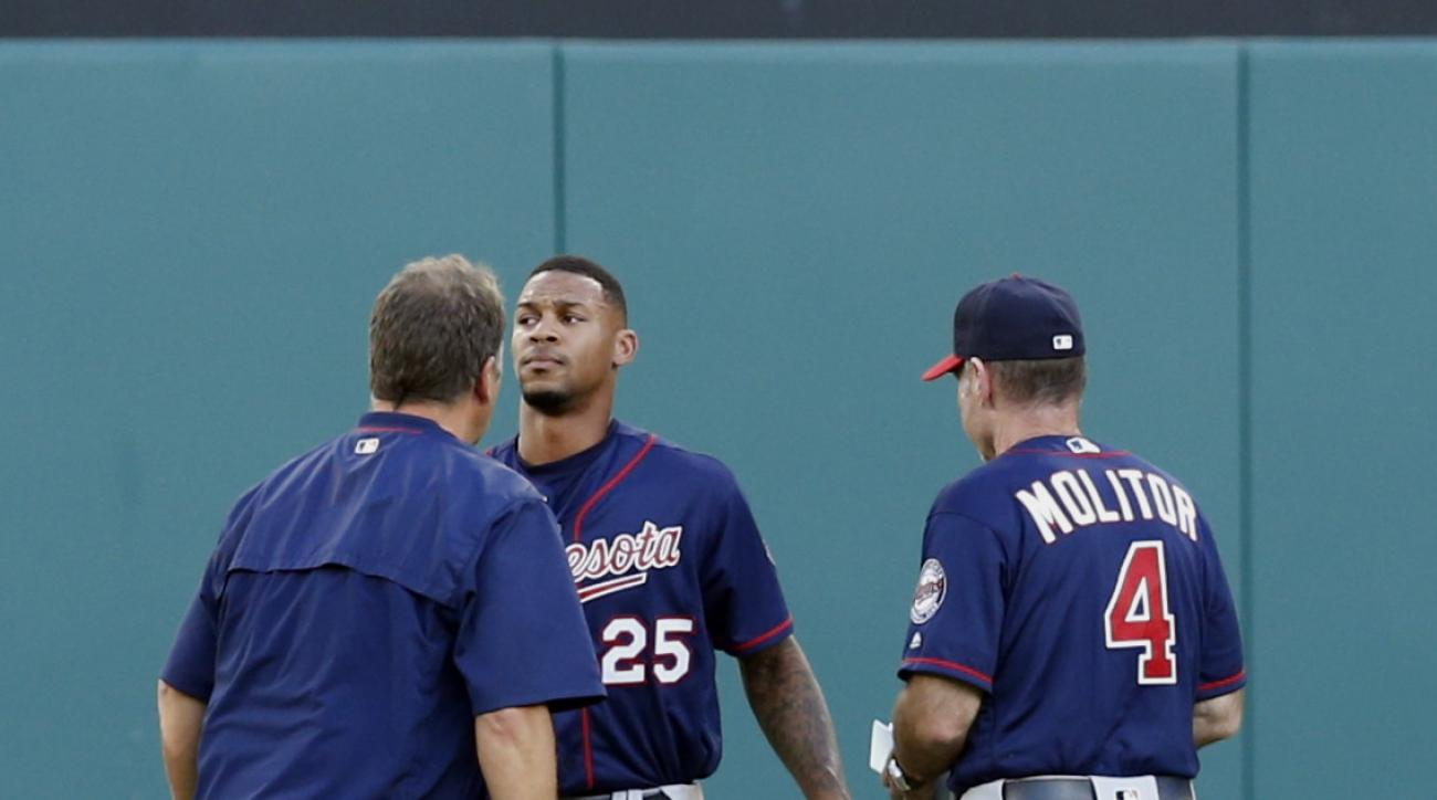 Minnesota Twins center fielder Byron Buxton (25) is checked by a team trainer and manager Paul Molitor (4) after colliding into the outfield wall on a ball hit by Texas Rangers' Rougned Odor during the first inning of a baseball game Friday, July 8, 2016,