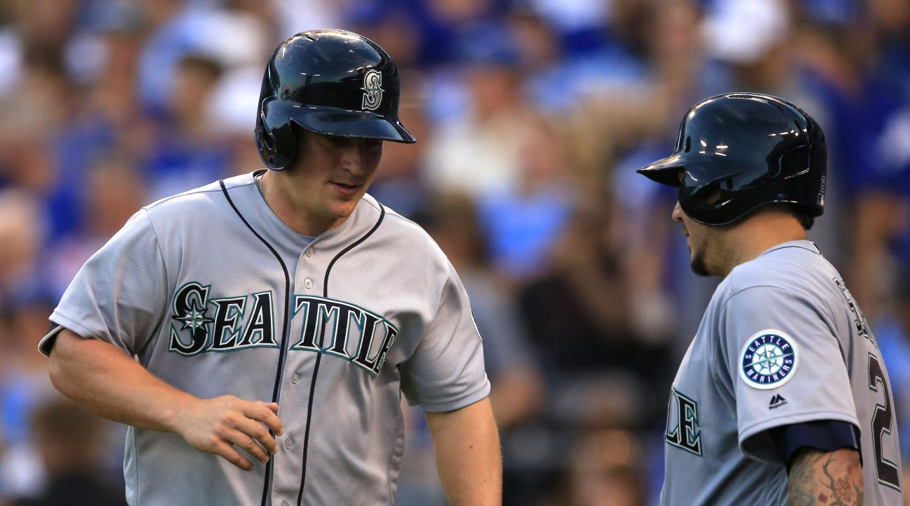 Seattle Mariners' Kyle Seager, left, is congratulated by teammate Jesus Sucre (2) after scoring on a sacrifice fly by Ketel Marte during the fifth inning of a baseball game against the Kansas City Royals at Kauffman Stadium in Kansas City, Mo., Friday, Ju