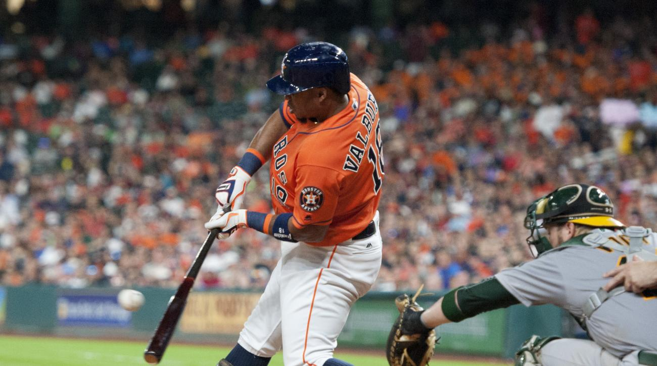 The Houston Astros Luis Valbuena, left, hits an RBI single against the Oakland Athletics in the fifth inning of a baseball game Friday, July 8, 2016, in Houston. (AP Photo/George Bridges)