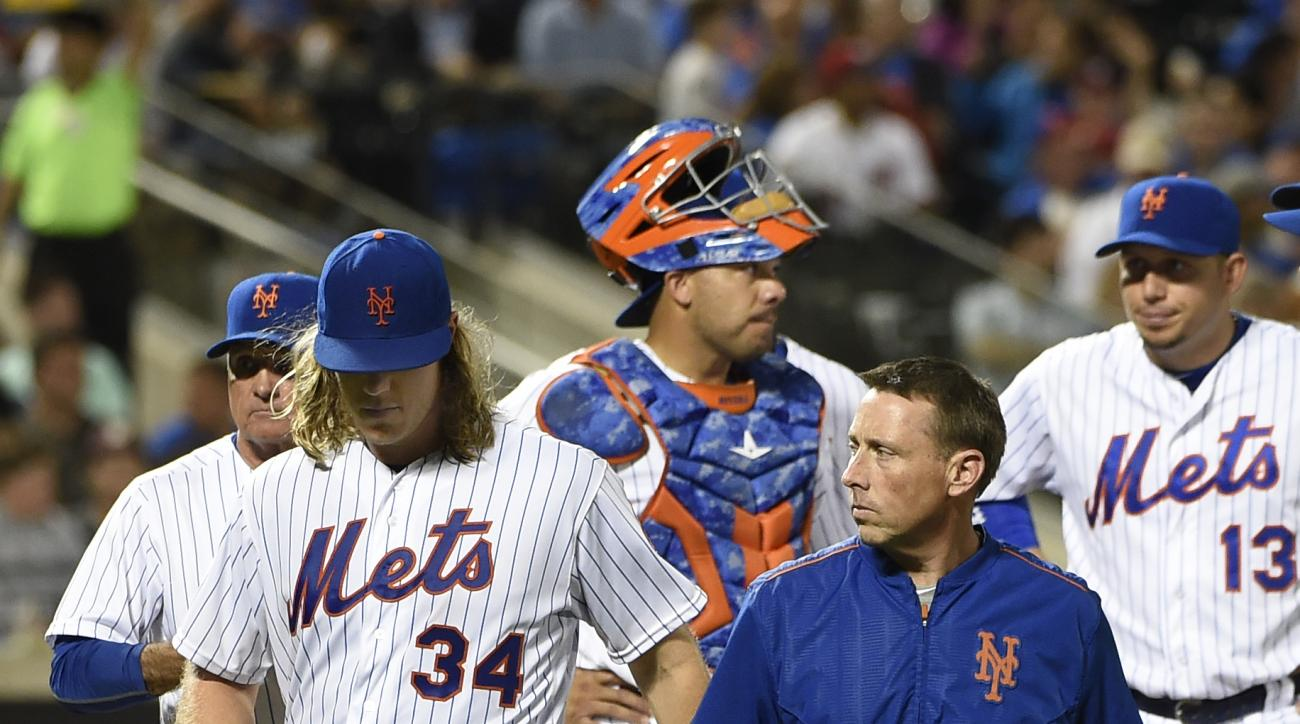 New York Mets starting pitcher Noah Syndergaard (34) is accompanied off the mound by a trainer after manager Terry Collins,  back left, removed him from a baseball game in the fifth inning, Friday, July 8, 2016, in New York. (AP Photo/Kathy Kmonicek)