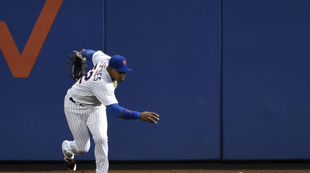 New York Mets center fielder Yoenis Cespedes reaches for Washington Nationals Daniel Murphy's fly ball in the third inning of a baseball game, Friday, July 8, 2016, in New York. (AP Photo/Kathy Kmonicek)