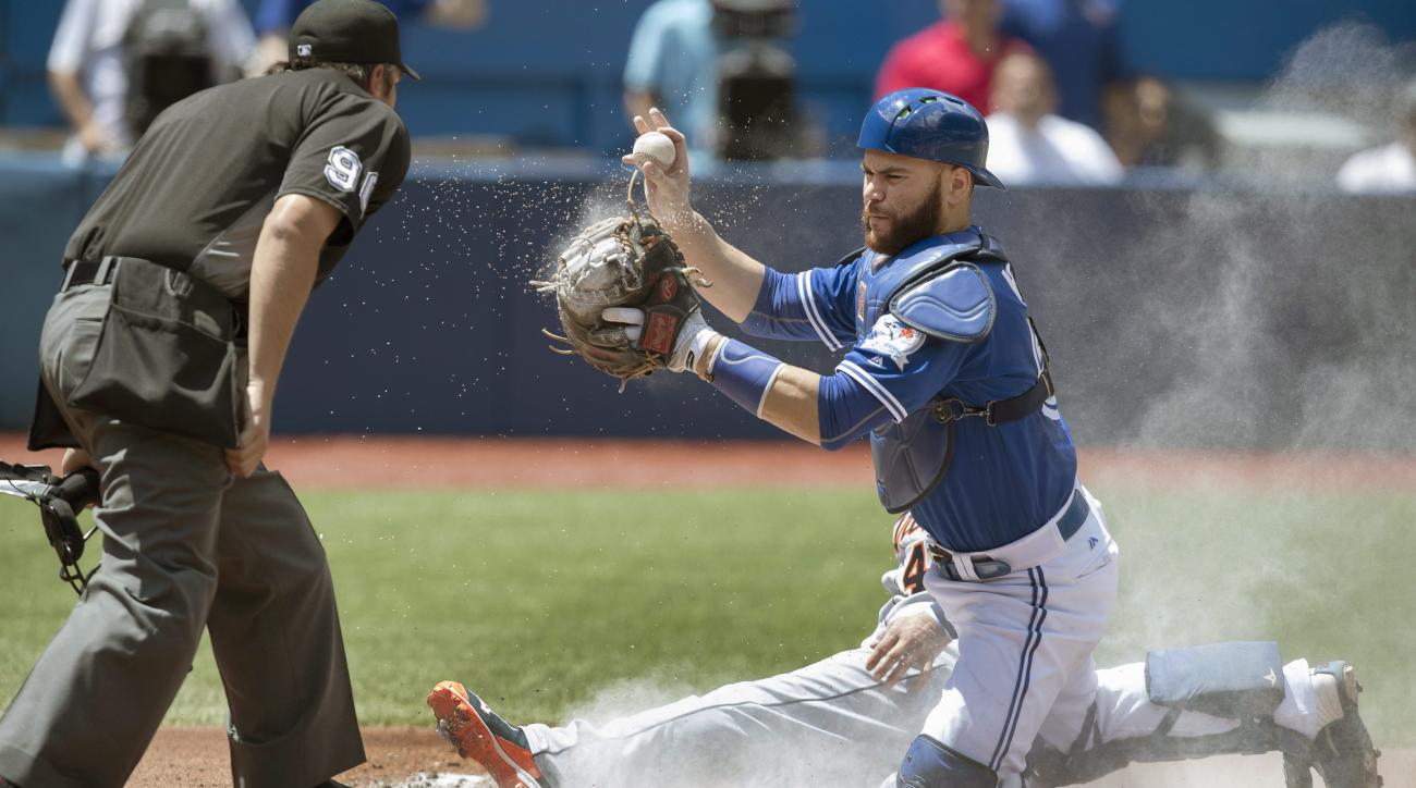 Toronto Blue Jays catcher Russell Martin comes up with the ball after tagging out Detroit Tigers' Victor Martinez during the second inning of a baseball game in Toronto, Saturday July 9, 2016. Umpire Mark Ripperger makes the call. (Fred Thornhill/The Cana