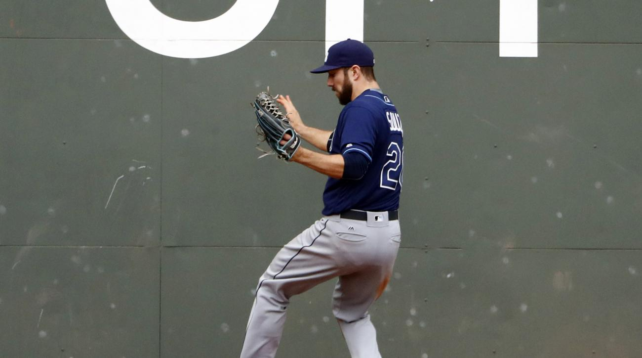Tampa Bay Rays center fielder Steven Souza Jr. drops the ball at the wall for an error on a hit by Boston Red Sox's Mookie Betts during the fifth inning of a baseball game at Fenway Park in Boston, Saturday, July 9, 2016. (AP Photo/Winslow Townson)