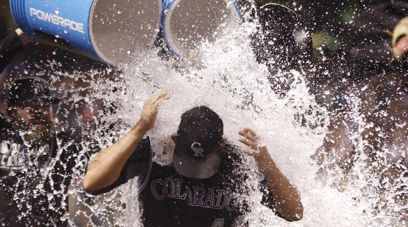 Colorado Rockies starting pitcher Tyler Anderson is doused by teammates Jason Motte, back left, and Brandon Barnes after a baseball game against the Philadelphia Phillies, Saturday, July 9, 2016, in Denver. Anderson had his first career win in the big lea