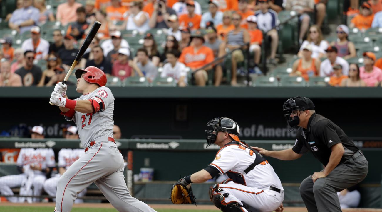 Los Angeles Angels' Mike Trout, left, doubles in front of Baltimore Orioles catcher Matt Wieters and home plate umpire Tim Timmons in the first inning of a baseball game in Baltimore, Sunday, July 10, 2016. Kole Calhoun scored on the play. (AP Photo/Patri