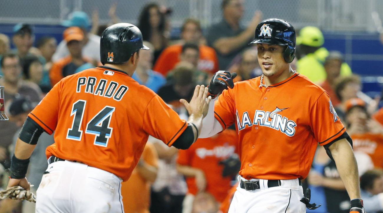 Miami Marlins' Giancarlo Stanton, right, is congratulated by Martin Prado (14) after hitting a two-run home run scoring Prado during the fifth inning of a baseball game against the Cincinnati Reds, Sunday, July 10, 2016, in Miami. (AP Photo/Wilfredo Lee)
