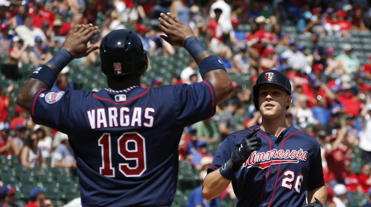 Minnesota Twins' Max Kepler (26) celebrates his grand slam home run as he arrives home with Kennys Vargas against the Texas Rangers during the fifth inning of a baseball game, Sunday, July 10, 2016, in Arlington, Texas. (AP Photo/Jim Cowsert)