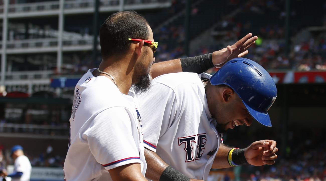 Texas Rangers' Rougned Odor, left, congratulates Elvis Andrus, right, after Andrus scored on a single by Bobby Wilson against the Minnesota Twins during the fifth inning of a baseball game, Sunday, July 10, 2016, in Arlington, Texas. (AP Photo/Jim Cowsert