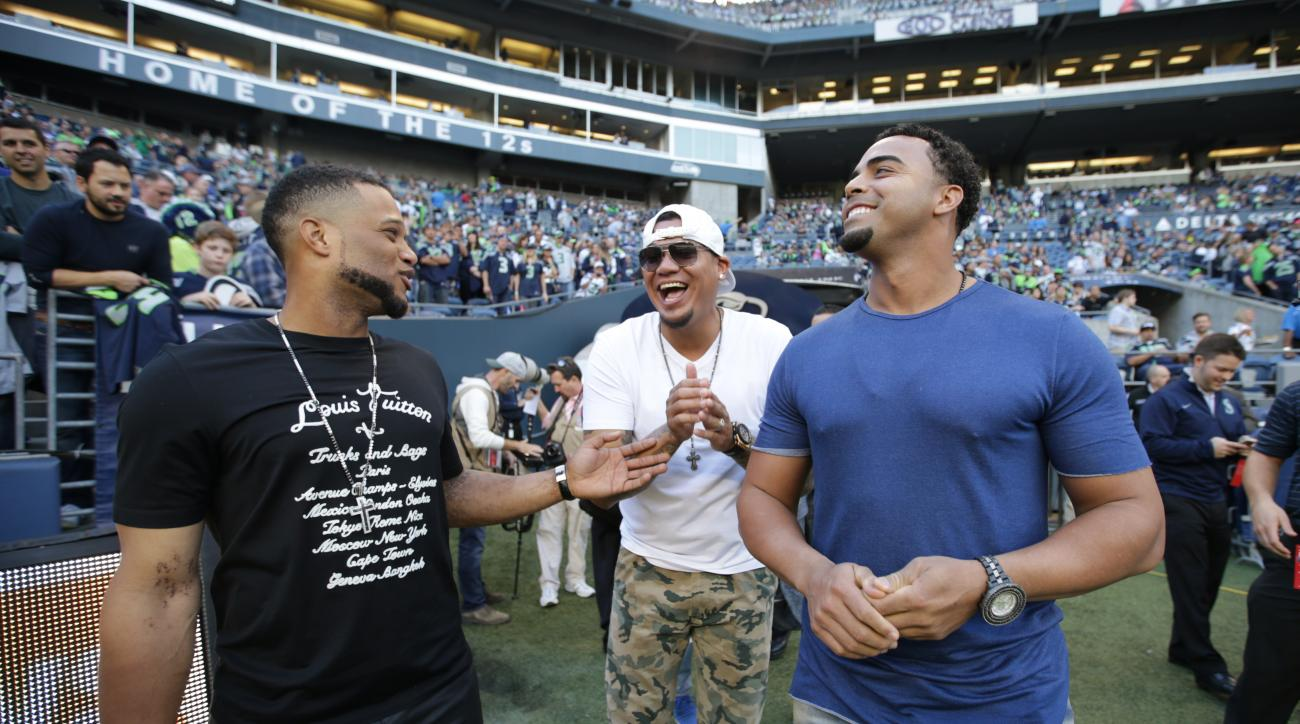 FILE - In this Oct. 5, 2015, file photo, from left, Seattle Mariners baseball players Robinson Cano, Felix Hernandez, and Nelson Cruz visit the Seattle Seahawks sideline before an NFL football game between the Seahawks and the Detroit Lions, in Seattle. A