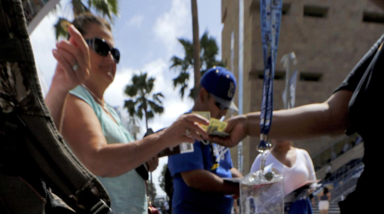 Fans purchase programs outside Petco Park prior to the MLB All-Star baseball Home Run Derby, Monday, July 11, 2016, in San Diego. (AP Photo/Matt York)