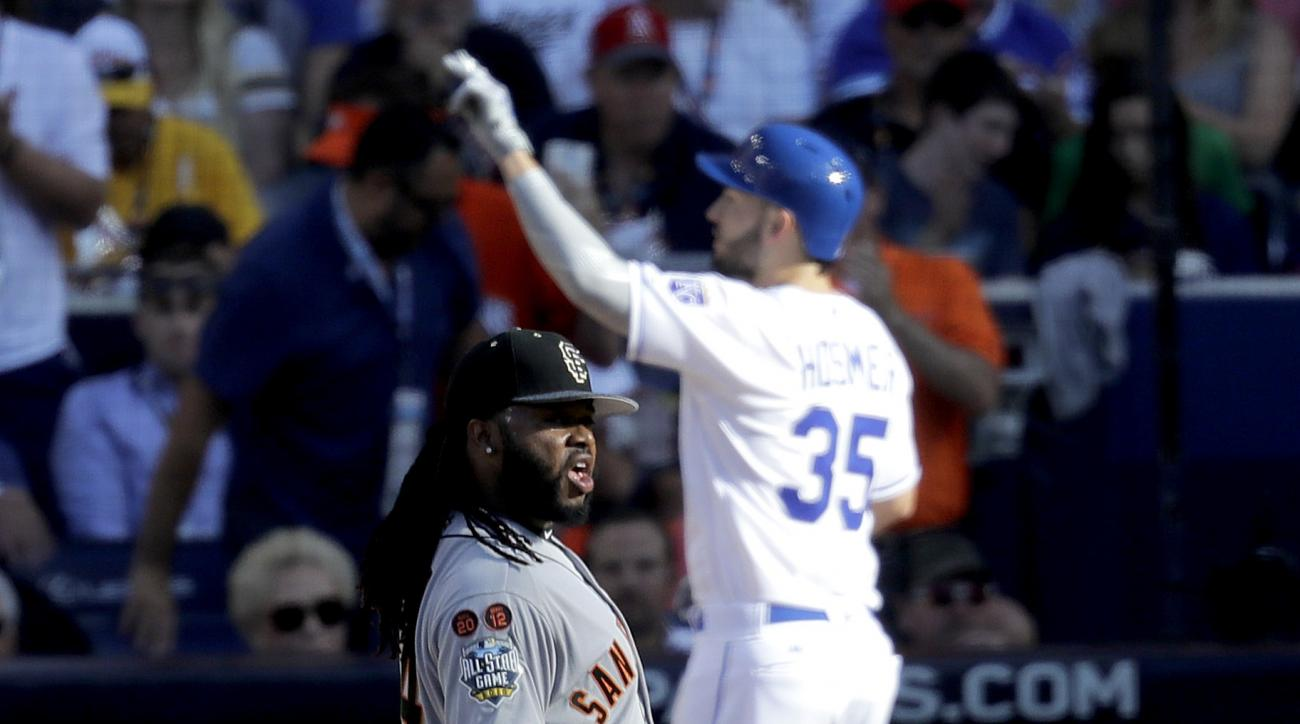 American League's Eric Hosmer, of the Kansas City Royals, crosses the plate after hitting a home run during the second inning of the MLB baseball All-Star Game, as National League's starting pitcher Johnny Cueto, of the San Francisco Giants, looks at the