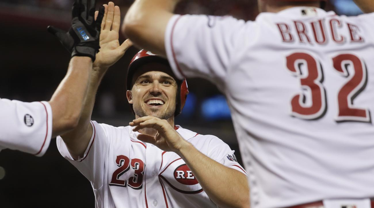 Cincinnati Reds' Adam Duvall (23) celebrates with Jay Bruce (32) and Anthony DeSclafani, after scoring on a two-run double by Tucker Barnhart off Milwaukee Brewers relief pitcher Carlos Torres during the sixth inning of a baseball game, Friday, July 15, 2