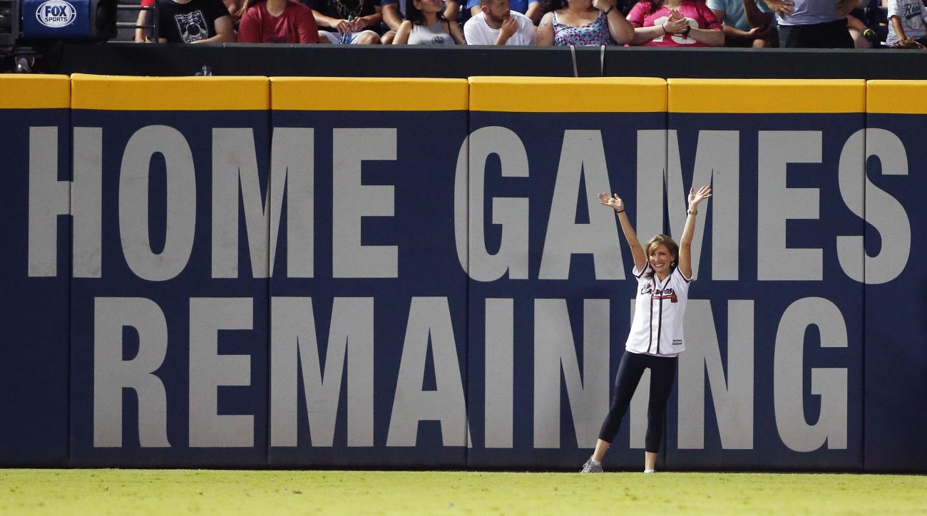 Olympic gold medalist former U.S. gymnast Shannon Miller waves to the crowd after changing the number of game left at Turner Field on the left field wall during of a baseball game between Colorado Rockies and Atlanta Braves Friday, July 15, 2016, in Atlan